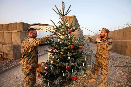 German Bundeswehr army soldiers decorate a fir tree imported from Germany for Christmas eve in the army camp in Kunduz