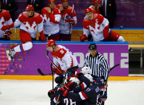Members of Team USA celebrate after defeating Russia in a shootout during their men's preliminary round ice hockey game at the Sochi 2014 Winter Olympic Games
