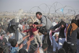 A Syrian refugee carries a baby over the broken border fence into Turkey after breaking the border fence and crossing from Syria in Akcakale, Sanliurfa province, southeastern Turkey, Sunday, June 14, 2015. The mass displacement of Syrians across the border into Turkey comes as Kurdish fighters and Islamic extremists clashed in nearby city of Tal Abyad. (AP Photo/Lefteris Pitarakis)
