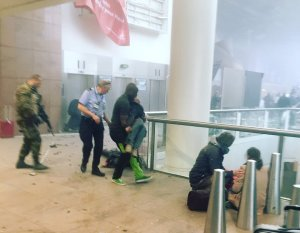 This photo provided by Georgian Public Broadcaster and photographed by Ketevan Kardava, shows the scene in Brussels Airport in Brussels, Belgium, after explosions were heard Tuesday, March 22, 2016. A developing situation left a number dead in explosions that ripped through the departure hall at Brussels airport Tuesday, police said. All flights were canceled, arriving planes were being diverted and Belgium's terror alert level was raised to maximum, officials said. (Ketevan Kardava/ Georgian Public Broadcaster via AP)